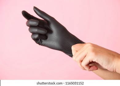 Wear rubber black glove on hand on pink background.