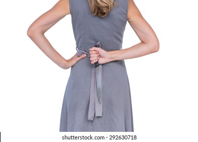 Wear view of woman hiding knife behind her back on white background