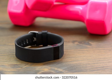 wearable device, wirst watch type Sports tracker and pink colored dumb-bell on a wooden board