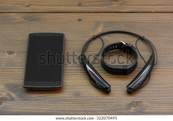 wearable device, wirst watch type Sports tracker with smartphone and wireless earphone on a wooden board