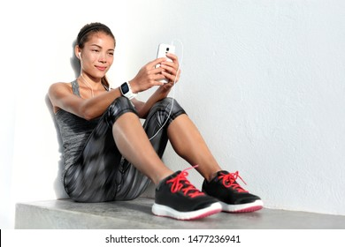 Wearable smart technology devices sport girl lifestyle wearing smartwatch using mobile phone listening to music app with earphones relaxing after fitness workout at gym. Asian woman fit and healthy.