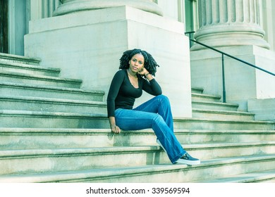Wearing black long sleeves, V neck top, blue jeans, leather sneakers, an African American college student sitting on stairs in office building in New York, relaxing. Filtered look with cyan tint.