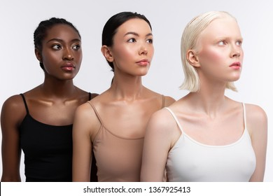 Wearing camisoles. Three young good-looking women with different skin color wearing camisoles