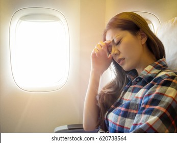 wearing casual style clothes lady take the plane feeling painful for head and hand putting on forehead express uncomfortable with film retro vintage color tone.