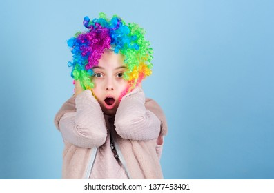 Wearing the foolish clown face. Surprised small clown with opened mouth. Adorable little girl wearing brightly colored clown hair wig. Everybody loves a clown, copy space.