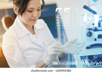 Wearing gloves. Calm attentive microbiologist sitting in the modern lab and putting on rubber gloves before working with samples
