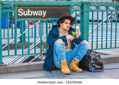 Wearing jacket with hood, destroyed jeans, boot shoes, Fedora hat, leather bag on ground, man with freckle face, sits on street by Subway sign in New York, looking at white rose.