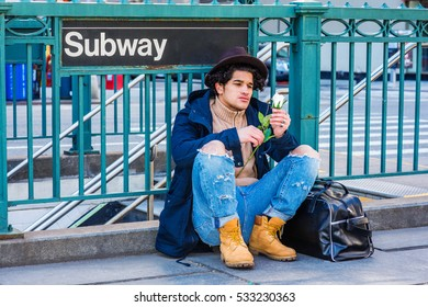 Wearing jacket with hood, destroyed jeans, boot shoes, Fedora hat, leather bag on ground, man with freckle face, sits on street by Subway sign in New York, looking at white rose. Color filtered effect