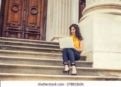 Wearing sleeveless orange shirt, striped pants, high heels, a young East Indian American college student sitting on stairs outside office building on campus, working on laptop computer, reading.