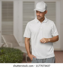 Wearing a white baseball cap, white polo shirt, and gray shorts outside on the patio looking to his right.