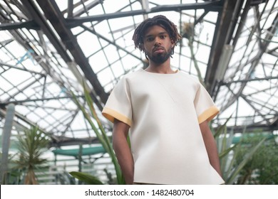 Wearing white t-shirt. Bearded handsome young man with dreadlocks wearing white t-shirt