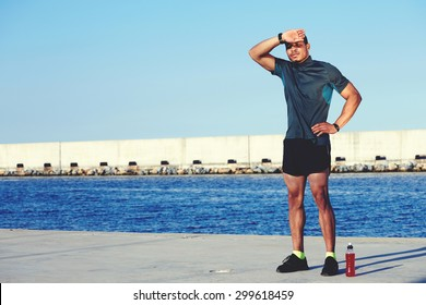 Weary sportsman rubbing his forehead while resting after workout against sea and sky background with copy space area for your text message or information, sweaty male runner taking break after jog