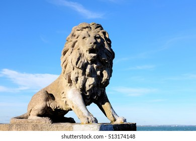 A weather beaten Lion statue overlooking the Solent on the banks at West Cowes on the Isle of Wight.