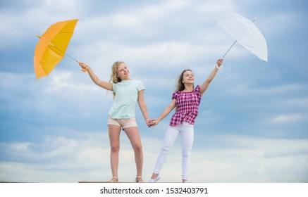 Weather changing. Girls friends with umbrellas cloudy sky background. Carefree children outdoors. Freedom and freshness. Weather forecast. Ready for any weather. Windy or rainy we are prepared.