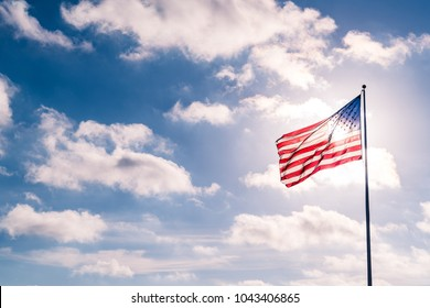 Weather clouds and sunshine summer sky with American flag illuminated back lit by sun. United States flag waving in the wind on a dramatic sky day