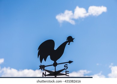 Weather cock against a cloudy sky