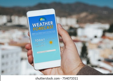 Weather forecast mobile phone app while man hold the smart phone in the hand, with the city in the background.