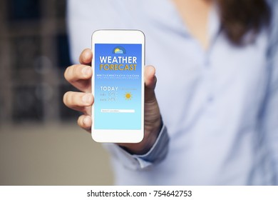 Weather forecast mobile phone app in a device screen. Woman hand holding it.