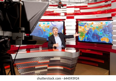 Weather forecast. A television anchorman at studio during live broadcasting