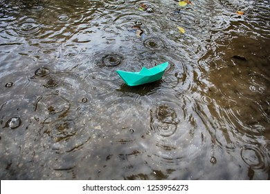 Weather in Israel, Winter. Paper Boat (Origami Ship) sails in a puddle during the rain, circles on the water and raindrops