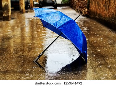 Weather in Israel, Winter. Rain, umbrella in the formed puddle, circles on the water and raindrops