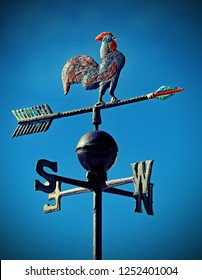 weather vane to indicate the wind direction with a rooster in wrought iron and arrows of Cardinal Points North East South West and old vintage effect