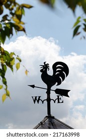 Weather vane sign on blue cloudy sky