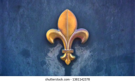 A weather-beaten copper fleur de lis symbol attached to blue concrete wall.