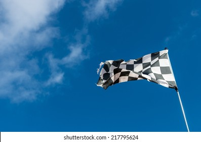 Weather-beaten racetrack finish flag or chequered flag.