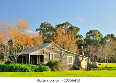 weatherboard house in lush winter garden under clear sky