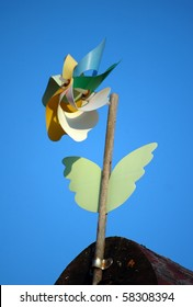 Weathercock in a shape of colorful flower with sky background
