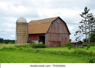 Weathered barn and silo with surrounding rural farmland and countryside