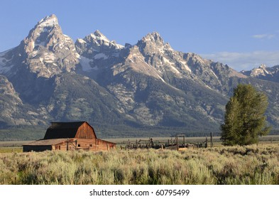 A weathered barn sits against the backdrop of the Grand Tetons in Wyoming, USA
