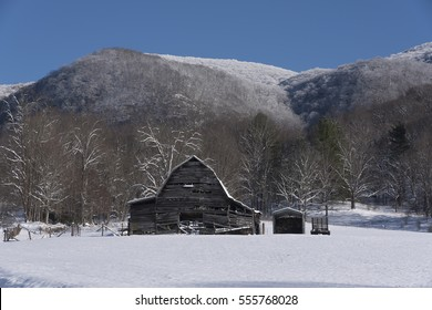 weathered barn in snow mountains