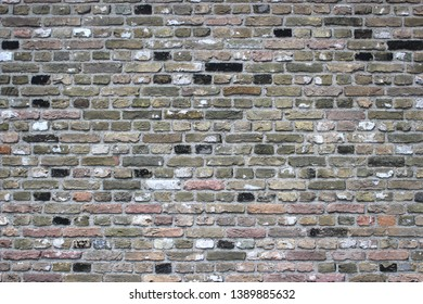 Weathered Brick wall texture background with color variations of black, earthy, reddish and white.