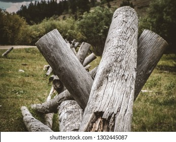 A weathered and broken cattle fence sits isolated and is falling down alongside a dirt road in a densely forested area.