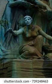 Weathered bronze statue of female.