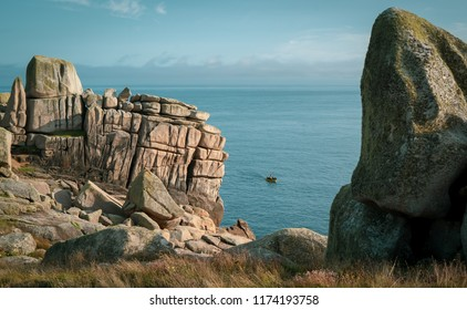 Weathered brown granite outcrops on the St Mary's coast, Isles of Scilly are lit by warm summer evening light. Through a gap in the rocks, fishermen can be seen coming in to check their lobster pots.