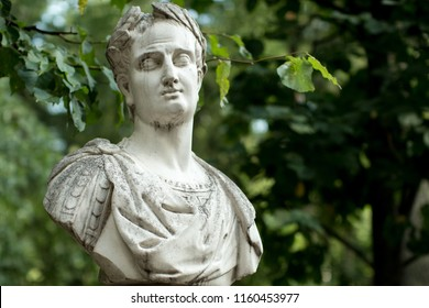Weathered bust monument to ancient Roman person with green foliage in background