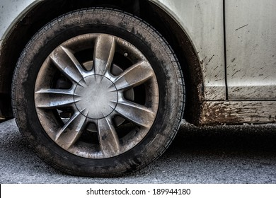 a weathered car wheel with mud and dirt