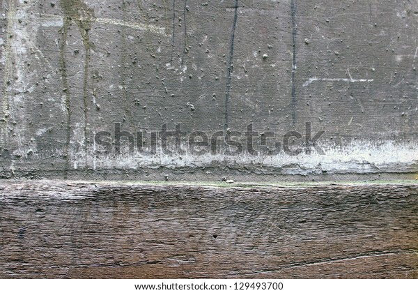 A weathered concrete and wood background wall.