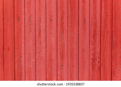 Weathered dark bright scarlet red painted vertical wooden plank wall with painted nails