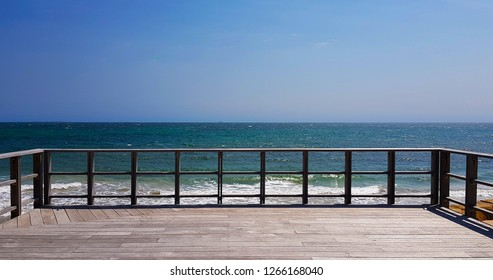 Weathered deck looking out onto a turquoise sea with some waves under a cloudless blue sky.