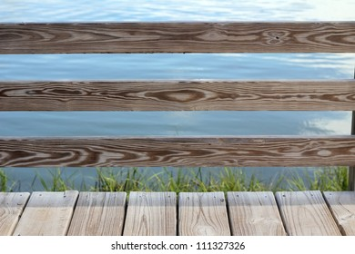 Weathered dock railing and boardwalk near the marsh of a river.