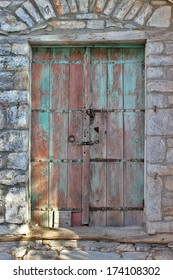 Weathered front door of an old stone house at south Pelion, Greece