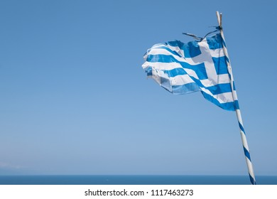 Weathered Greek flag blowing in the wind.