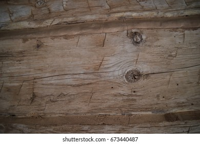 Weathered hand-hewn wooden log cabin beams