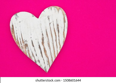 Weathered heart on bright pink textured felt material with copy space for your message