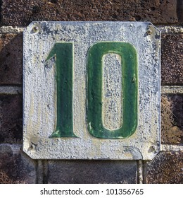 weathered house number ten. Green font on white background