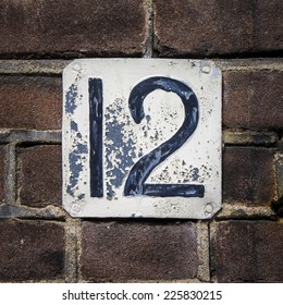 weathered house number twelve. Black numerals on a white plate.